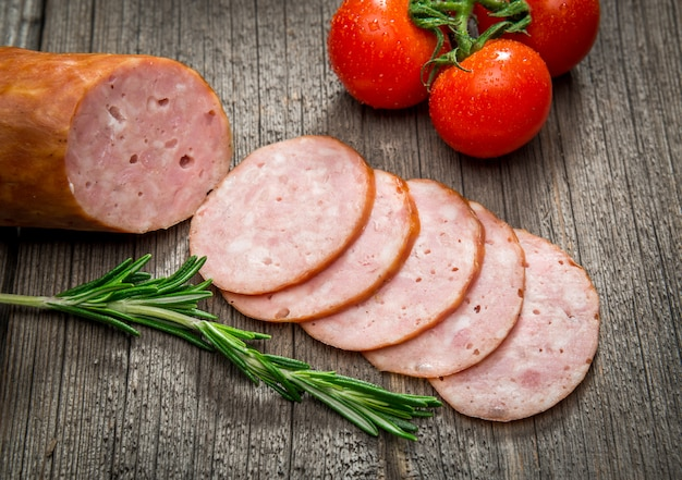Salami sausages sliced with pepper, garlic and rosemary on cutting board on wooden table. top view