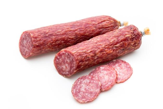 Копченая колбаса салями, листья базилика и перец горошком, изолированные на белой поверхности.