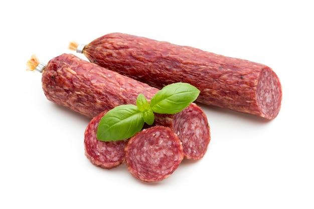 Копченая колбаса салями, листья базилика и перец горошком, изолированные на белом.