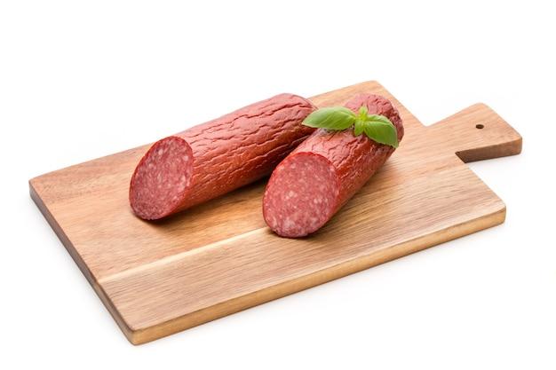 Колбаса копченая салями, листья базилика на белом вырезе. Premium Фотографии