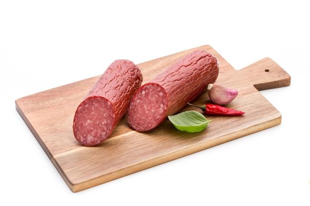 Колбаса копченая салями, листья базилика на вырезе белой поверхности.