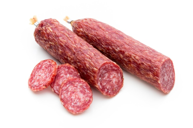Salami smoked sausage, basil leaves and peppercorns isolated on white surface.