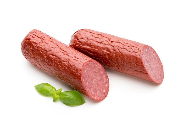 Salami smoked sausage, basil leaves on white  cutout.