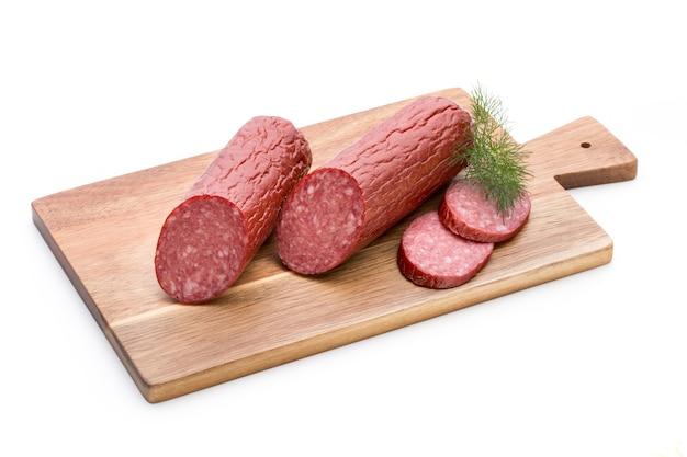 Salami smoked sausage, basil leaves on white surface cutout.