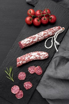 Salami and tomatoes on desk