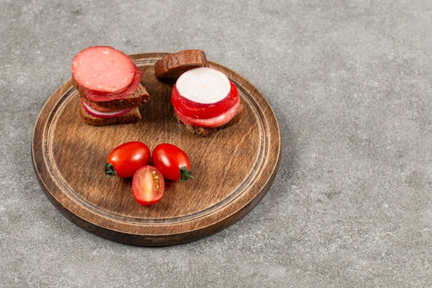 Salami and vegetable sandwich on wooden board.