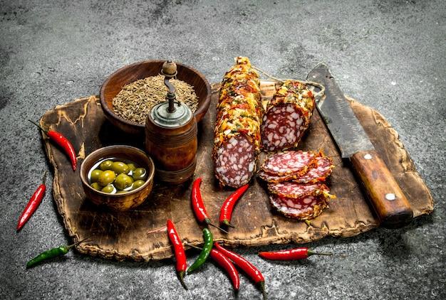 ボードにスパイスと唐辛子を添えたサラミ。素朴なテーブルの上。