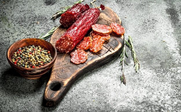 Salami with spices and herbs. on a rustic table.