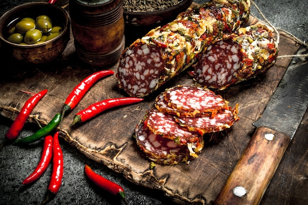 Salami with spices and hot peppers on the board. on a rustic table.