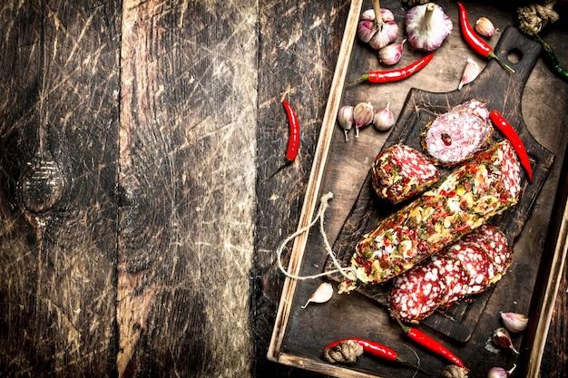 古いトレイにスパイスを入れたサラミ。木製の背景に。