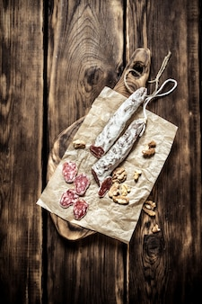 Salami with walnuts on old paper on wooden table.