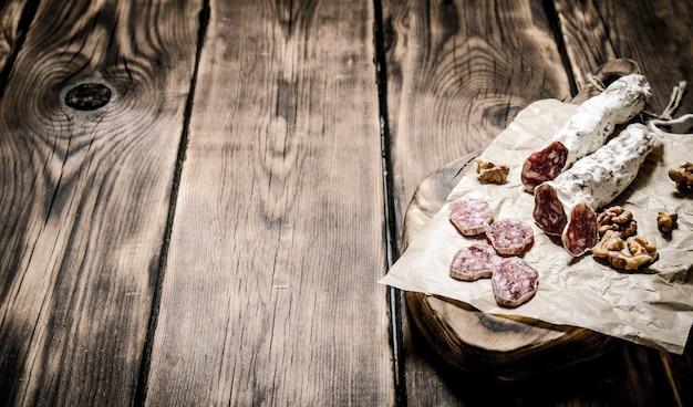 Салями с грецкими орехами на старой бумаге на деревянном столе.