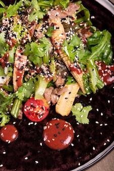 Салат из рукколы и мяса на черной тарелке