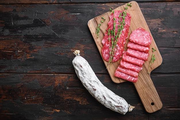 Колбасы салчичон вяленые, нарезанные ломтиками на темном деревянном фоне, вид сверху с пространством для текста.