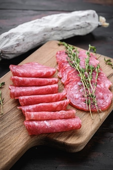 Salchichon sausages cut in slices  on old wooden table
