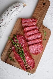 Салчичон, целые и нарезанные ломтики, испанская колбаса на белой поверхности, плоская выкладка.