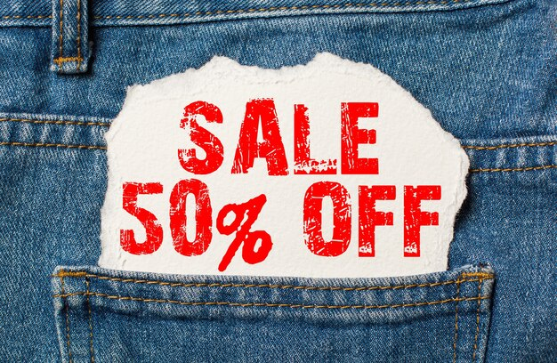 Sale 50 off on white paper in the pocket of jeans