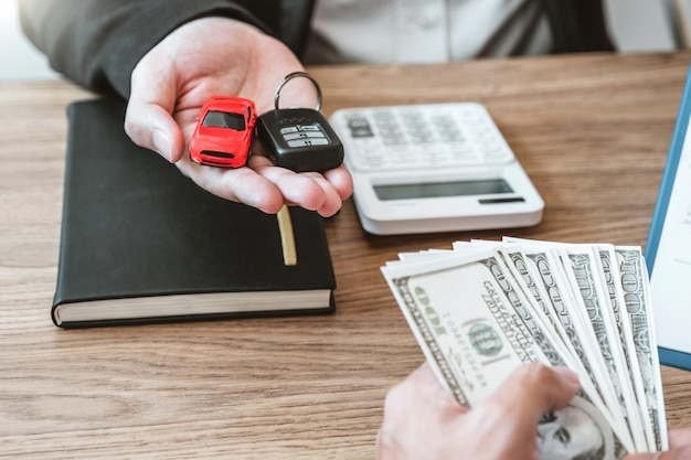 Sale agent giving car key to customer and sign agreement contract, insurance car .