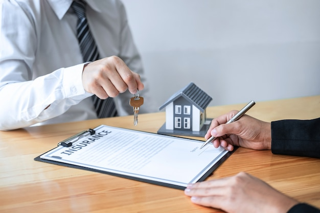 Sale agent giving house key to new client after signing agreement contract