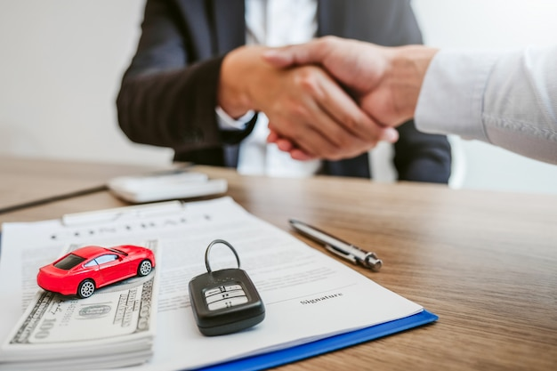 고객 및 서명 계약 계약을 가진 성공적인 자동차 대출 계약을 판매 에이전트 악수 거래 보험 자동차 개념입니다.