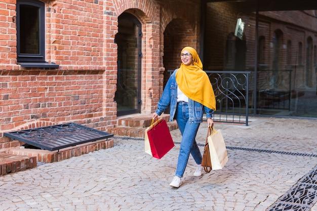 販売と購入の概念-モールの後に買い物袋を持つ幸せなアラブのイスラム教徒の少女