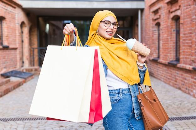 販売と購入の概念-モールの後に買い物袋を持つかなりアラブのイスラム教徒の少女