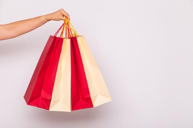 판매 및 소비 개념. 흰색 위에 쇼핑백과 여성 손 클로즈업
