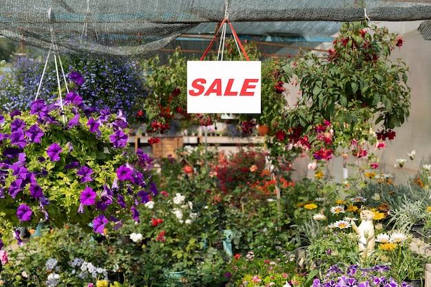 温室や花屋の中にあるさまざまな花の上にぶら下がっている紙にセールのお知らせ