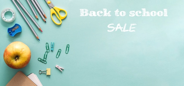 Sale back to school concept.wooden colored pencils,blank school notebook, paper clips apple and other office supplies on blue background. pencils for drawing objects for creativity.mock up copy space