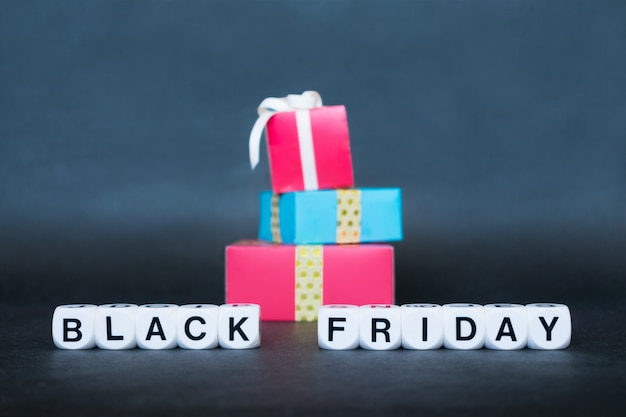 Sale banner with text word black friday and multicolored gift boxes.