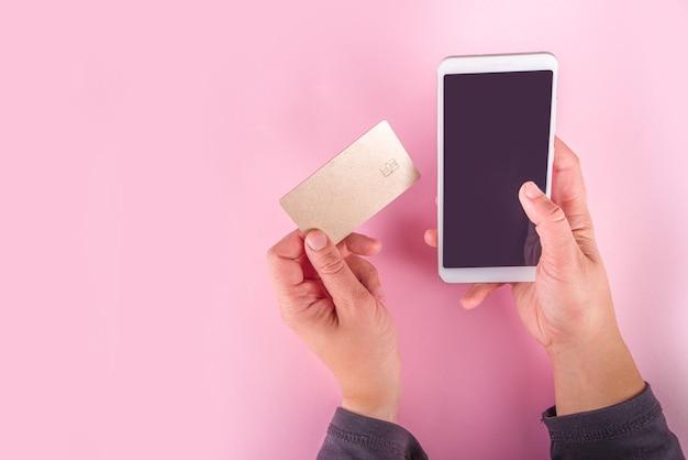 赤緑の紙袋、ショッピングカート、銀行カード、コンピューターのキーボード、女の子の手にスマートフォンのトップビューフラットレイのショッピングとブラックフライデーの背景を販売