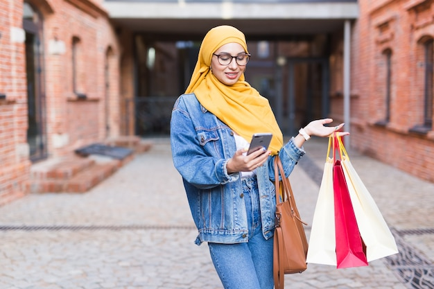 Sale and buying concept - happy arab muslim girl with shopping bags after mall holds mobile phone