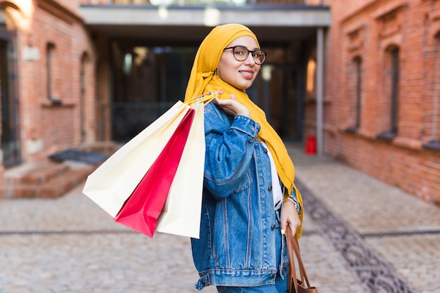 Sale and buying concept - happy arab muslim girl with shopping bags after mall