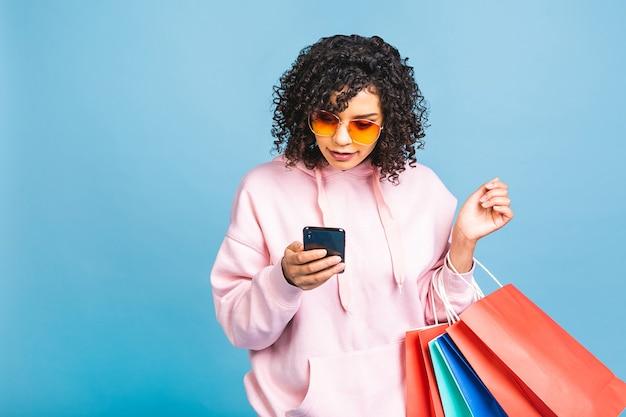 セールコンセプト!青い背景に分離されたショッピングバッグを笑顔で保持している美しい黒人アフリカ系アメリカ人女性。携帯電話を使う。