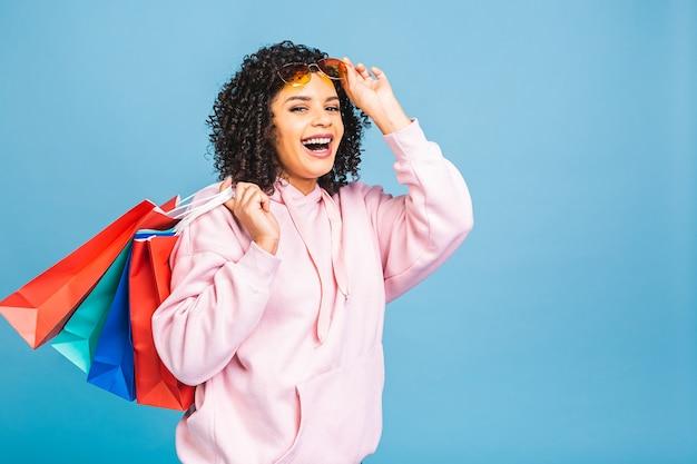 セールコンセプト!青い背景に分離されたショッピングバッグを笑顔で保持している美しい黒人アフリカ系アメリカ人女性。