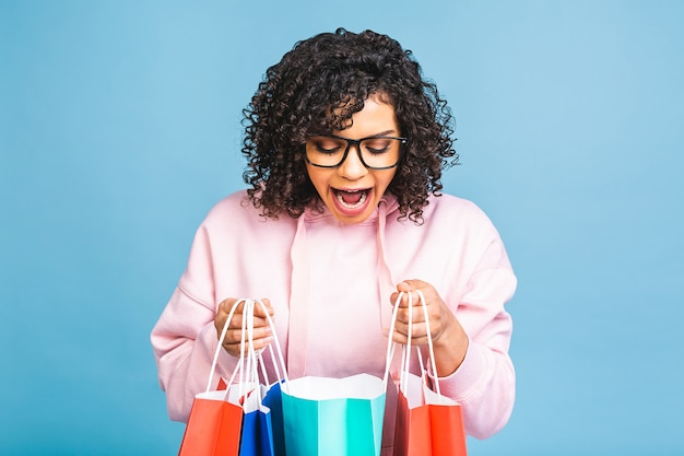 セールコンセプト!笑顔と青い背景で隔離の買い物袋を保持している美しい黒人アフリカ系アメリカ人女性。