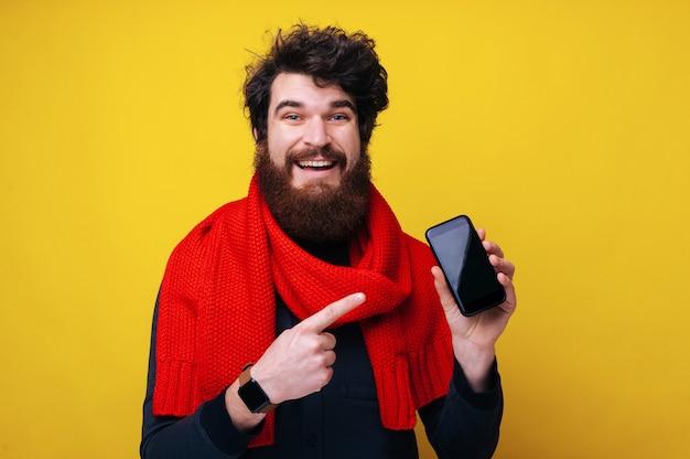販売コンセプト。黄色の背景の上に、赤いスカーフを身に着けて、カメラを見ながらモバイル画面を指している陽気なひげを生やした男