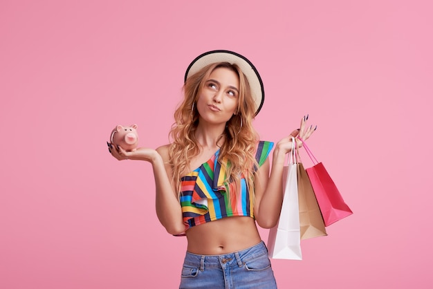 Sale concept. portrait of a happy pretty girl in stylish hat holding shopping bags and piggy bank.