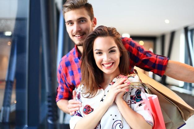 販売、消費主義、人々のコンセプト-モールを歩いている買い物袋を持つ幸せな若いカップル。