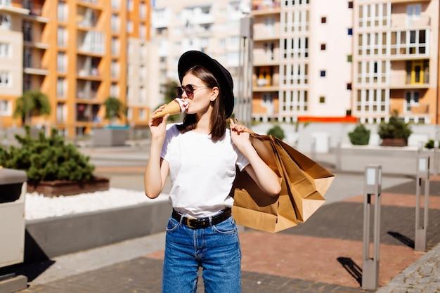 판매, 소비, 여름 사람들 개념. 쇼핑백과 도시 거리에 아이스크림 행복 한 젊은 여자