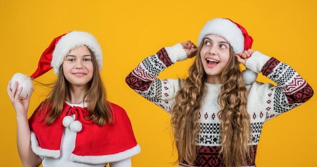 선물 및 선물 판매. 우정 개념입니다. 행복한 산타클로스 아이들. 빨간 산타 모자와 스웨터에 웃는 아이. 겨울 휴가를 축하합니다. 크리스마스 쇼핑 시간. 십대 소녀들은 행복을 느낍니다.