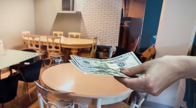 Sale of furniture in the store, the buyer pays the cashier for his goods. dollar in hands