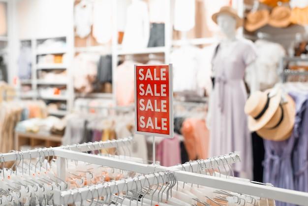 衣料品店のレディースコーナーでの販売。碑文セール、ショップでの割引、ぼやけた背景の赤い看板。ブラックフライデー、セールコンセプト