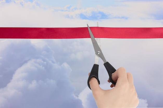 Продажа авиабилетов. открытие границ стран, начало путешествия. рука ножницами перерезает красную ленту, глядя на пушистые облака в голубом небе.