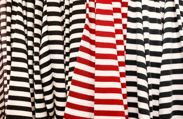 상점에서 의류 판매 빨간색과 검은색 줄무늬가 있는 줄무늬 티셔츠의 질감