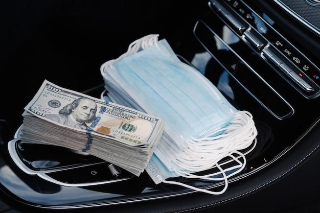 의료용 마스크 판매. 달러 지폐와 얼굴 마스크 자동차의 스택. 코로나 바이러스 확산 동안 수익성있는 사업. 건강 관리 개념입니다. 유행성 상황. 판매 투기. 금융 위기
