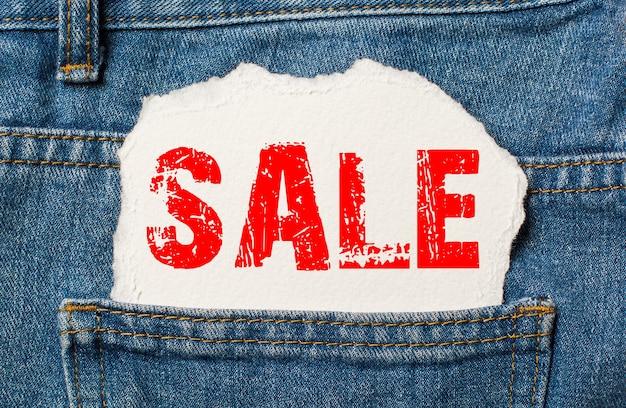 Распродажа на белой бумаге в кармане джинсов