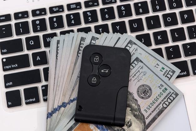 노트북 키보드 클로즈업을 통해 달러 지폐와 함께 판매 온라인 구매 개념 자동차 키