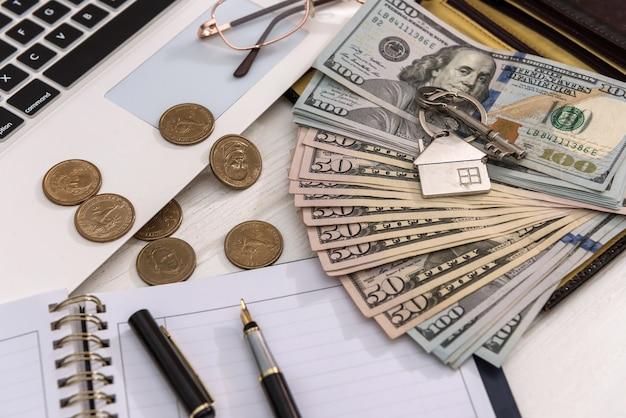 달러 지폐와 노트북 판매 또는 임대 개념 홈 키 저장