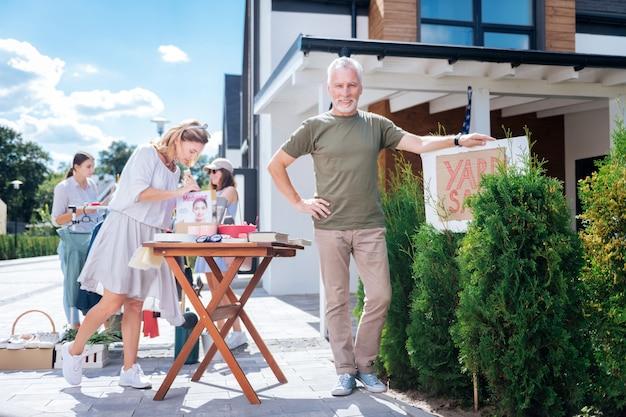 Организатор продаж. красивый зрелый мужчина в бежевых брюках и рубашке цвета хаки организует распродажу во дворе в теплый летний день